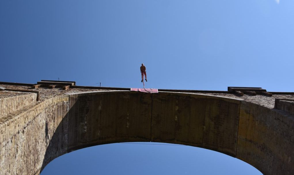 Seen from the ground silhouette of bungee jumper falling down from a high stone bridge, summer day with blue sky