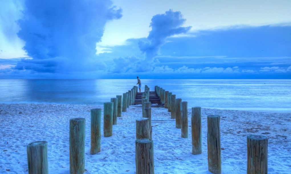 Fisherman stands on an old pier at the ocean on Naples Beach with dark skies overhead and rain on the horizon in Naples, Florida