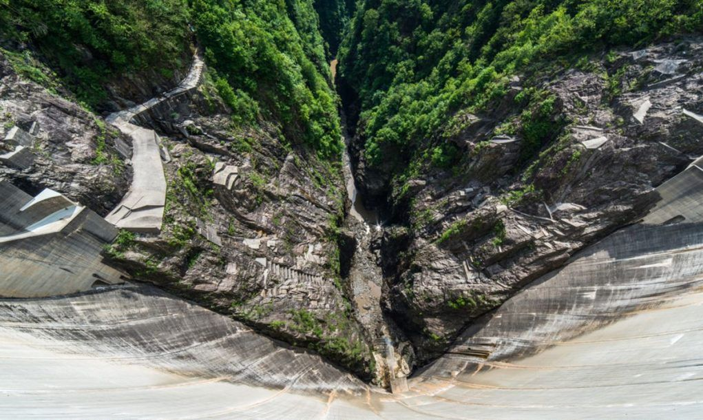 Wide angle-lens shot of a man staying at the edge of Contra Dam, Verzasca, Ticino, Switzerland
