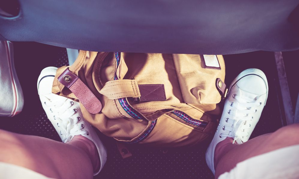 Close up sneaker white shoe with backpack on floor under airplane seat,