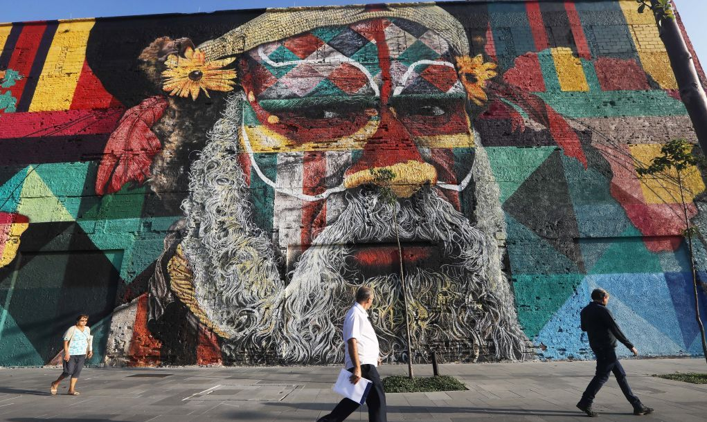 RIO DE JANEIRO, BRAZIL - MAY 31: People walk past street art created by Eduardo Kobra decorating a building in the Port District, an area revamped ahead of the Rio 2016 Olympic Games, on May 31, 2017 in Rio de Janeiro, Brazil. While the Rio 2016 Olympic Games are generally regarded as having left Rio with a mixed legacy at best, an abundance of street art has flourished in the cityÕs renovated Port District.