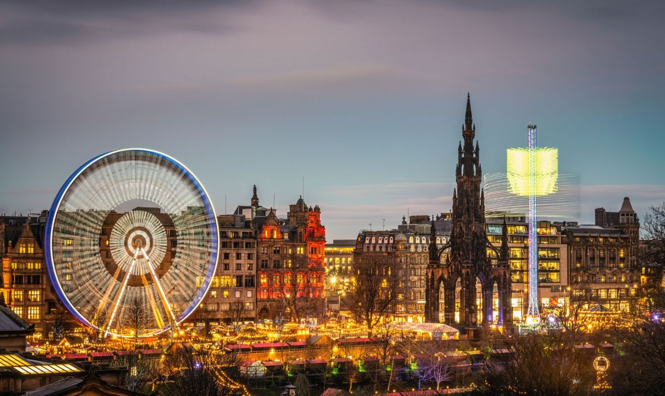 Amusement rides on Princes Street in Edinburgh's city centre, blurred by motion at dusk.