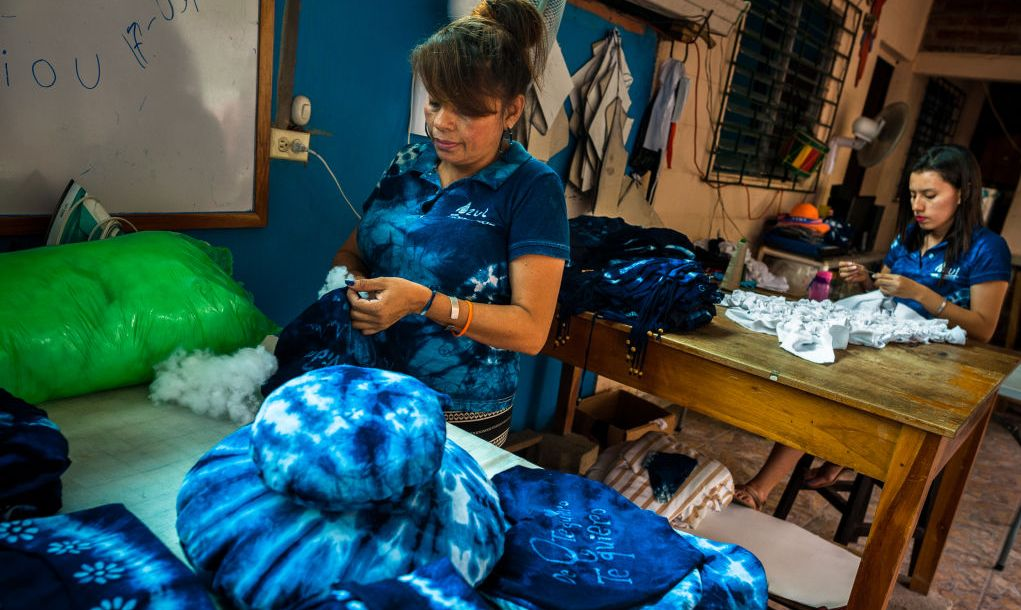 A Salvadoran woman stuffs a decorative pillow, dyed with a natural blue indigo, at an artisanal clothing workshop on April 6, 2018 in Santiago Nonualco, El Salvador. For centuries the indigo, a natural deep blue dye extracted from the leaves of tropical plants (Indigofera), has been known by the native indigenous of Central America who used the blue tincture to color their fabrics and pottery. Due to the growing demand of natural-based products, clothing workshops have emerged in the country.
