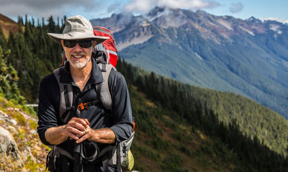 Hiker poses in front of mountain peaks