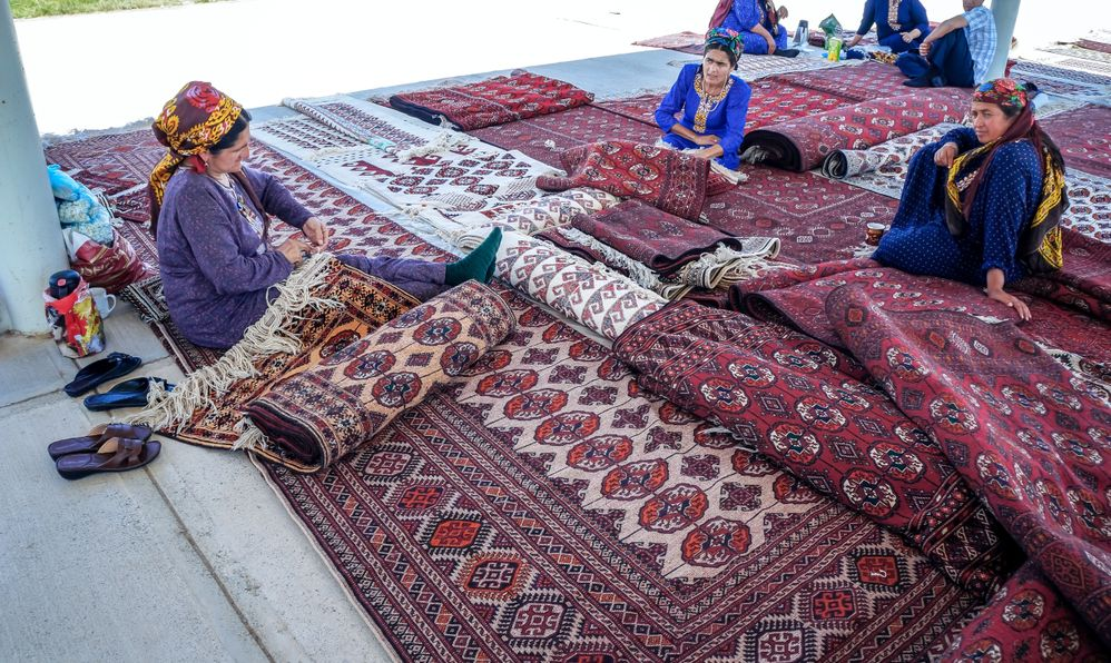 Women selling traditional carpets at Altyn Asyr bazaar known as Taze Jygyldyk or New Tolkuchka, largest open air market in Central Asia.