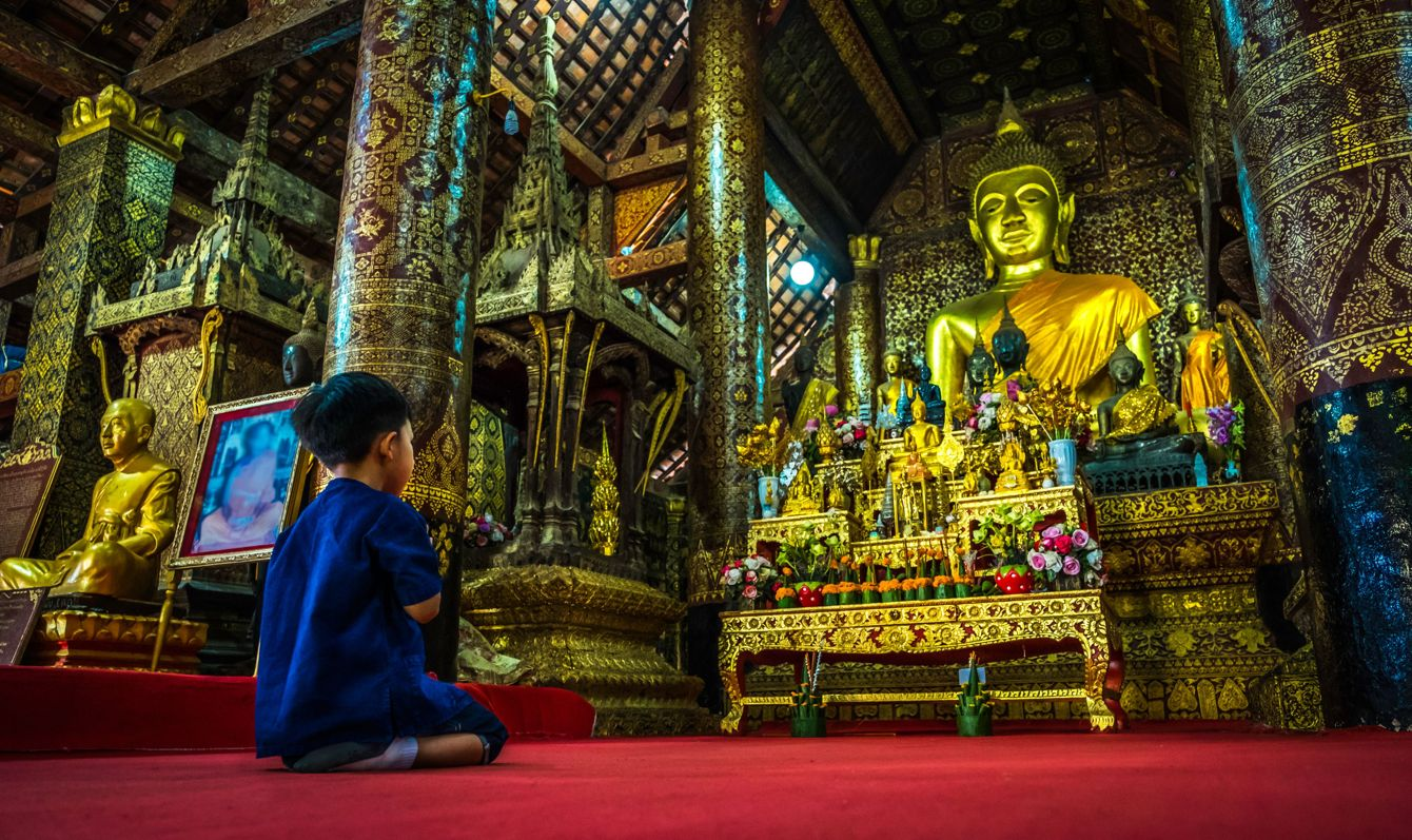 Asian boy pay respect Buddha at Wat Xieng thong temple at twilight time in Luang Pra bang, Laos