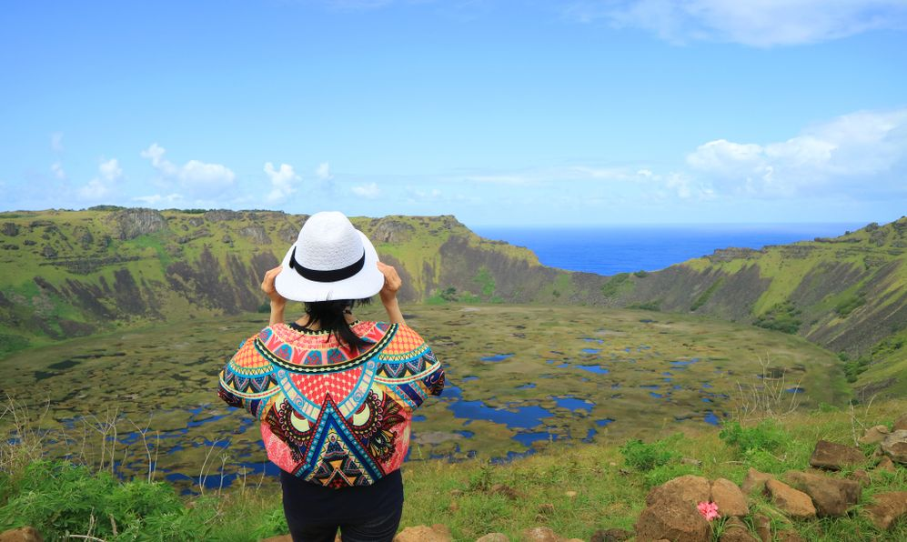 Female Appreciating the Breathtaking View of Rano Kau Crater Lake from Orongo Ceremonial Village on Easter Island with Pacific Ocean in the Distance, Chile