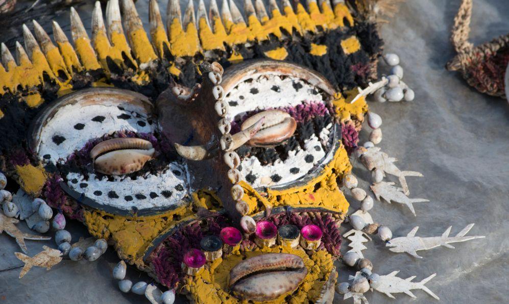Folk art souvenir mask adorned with seashells and crocodile teeth