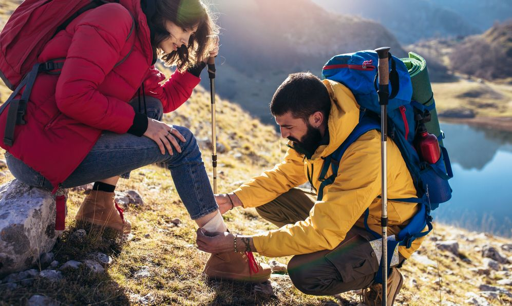 A woman has sprained her ankle while hiking, her friend uses the first aid kit to tend to the injury - Image