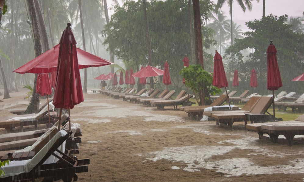 storm on the beach, heavy tropical rain in tourist hotel resort
