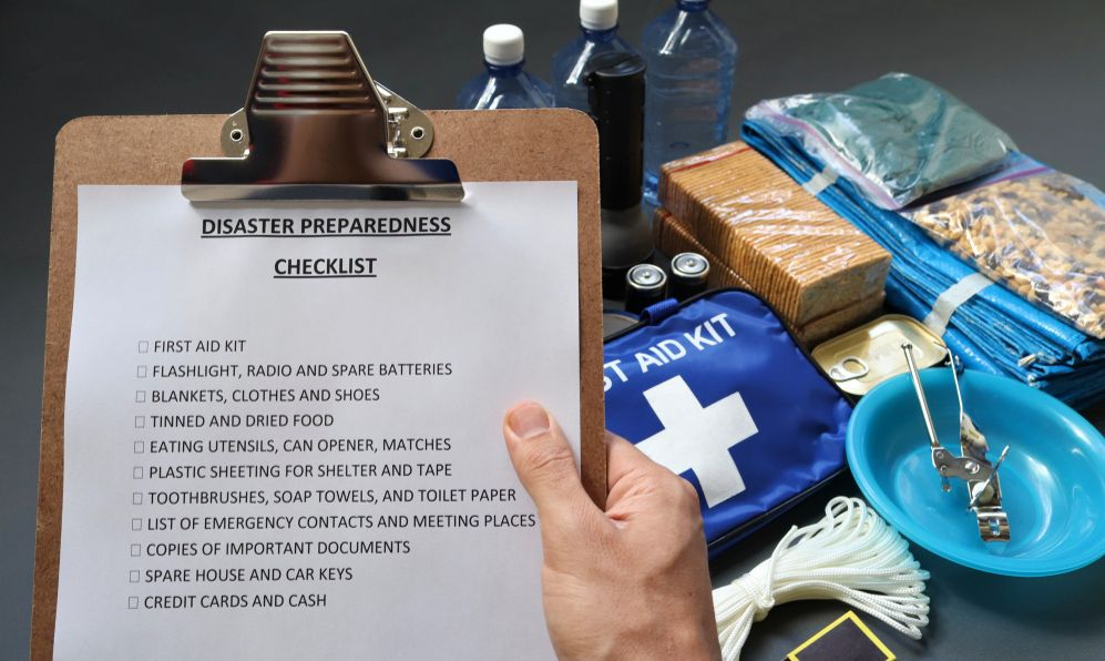 Disaster preparedness checklist on a clipboard with disaster relief items in the background