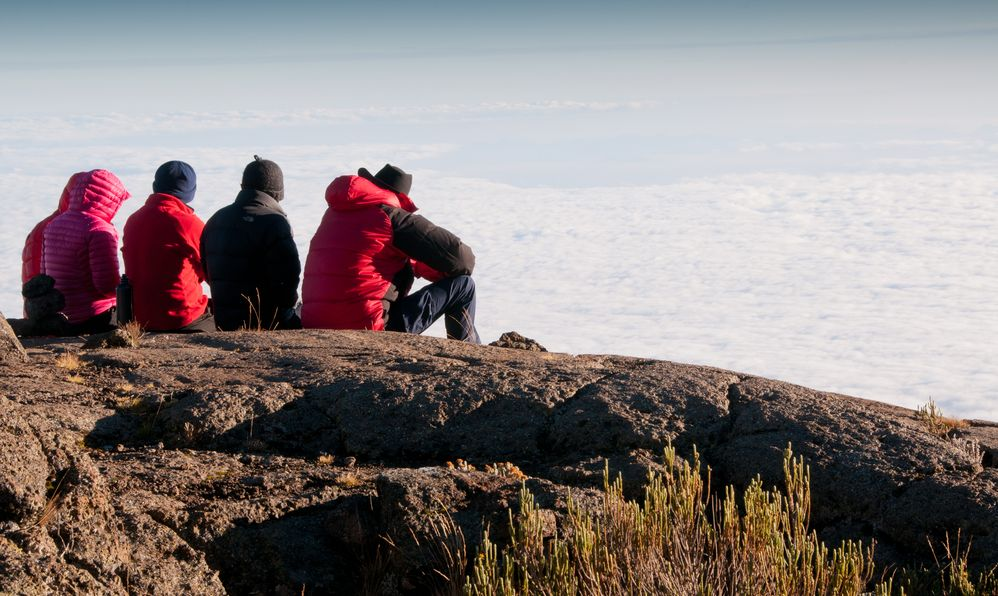 A team of trekkers gazing over the early morning clouds on the trek to Kilimanjaro summit