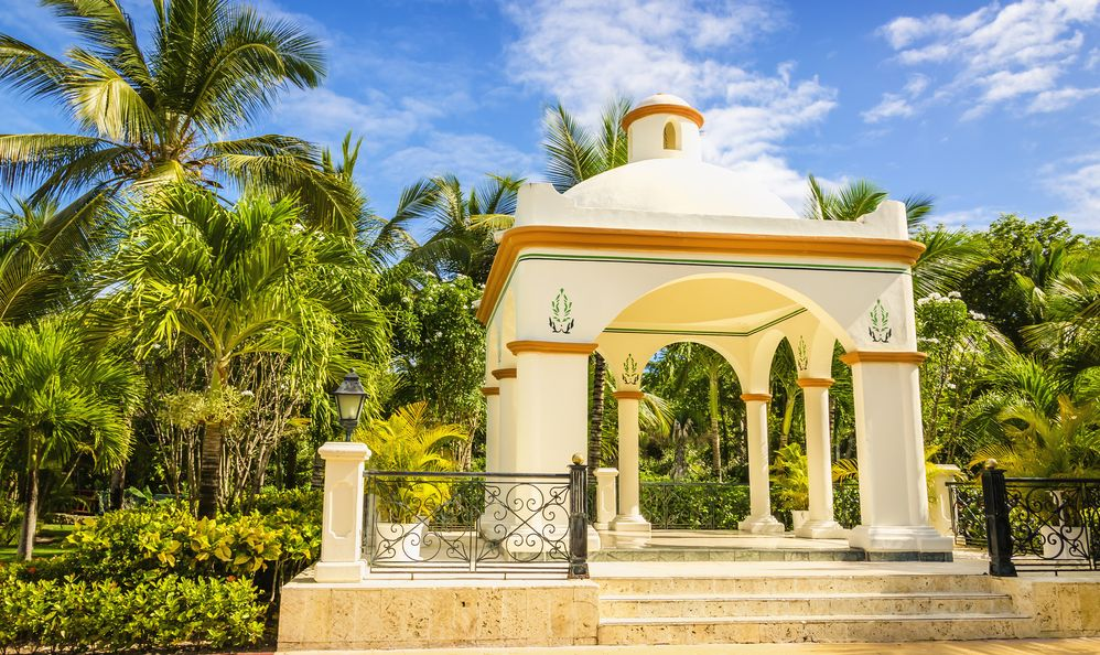 Wedding gazebo on one of Caribbean Islands, tall exotic palm trees and blue sky.