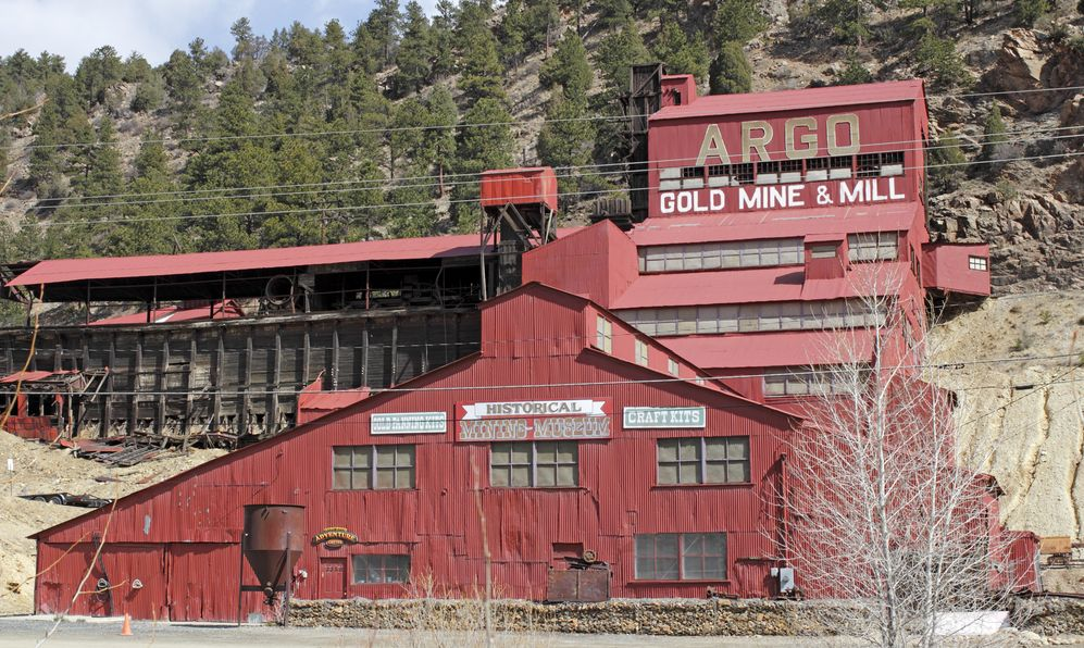 Large, red painted Argo gold mine and mill with a historical mining museum in front of a rising mountain.