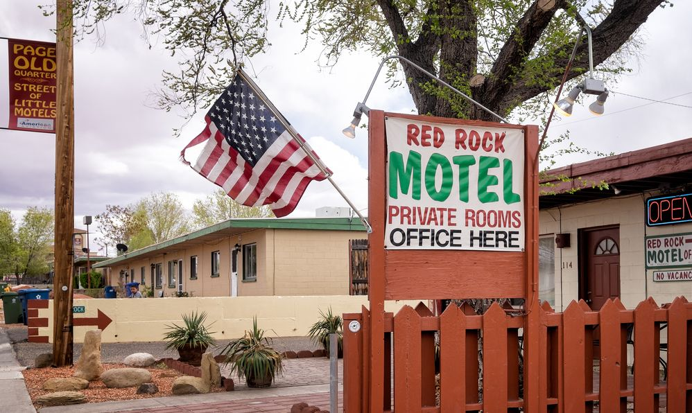 Vintage mid-century motel in the town's historic district. Red Rock Motel exterior with an American flag and sign reading Street of Little Motels