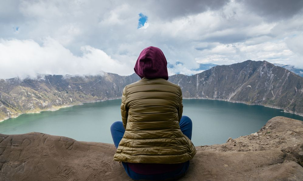 """Unidentified woman next to Quilotoa a water-filled caldera and the most western volcano in the Ecuadorian Andes and a popular tourist destination with many hiking paths including the """"Quilotoa Loop""""."""