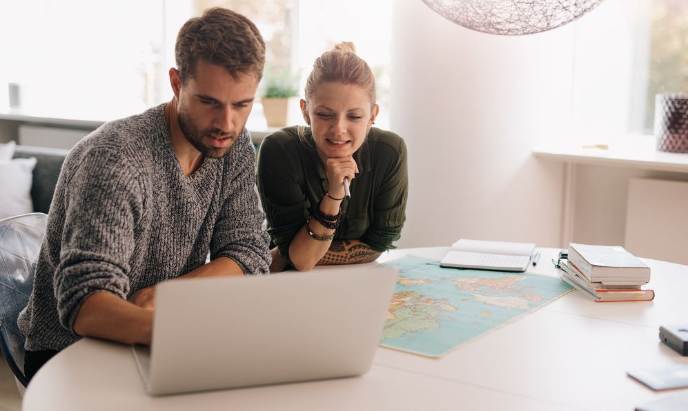 Young man and woman sitting with world map and computer on study table