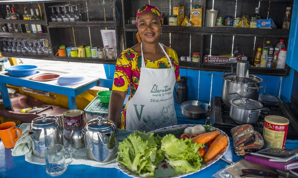 Woman in the kitchen of a tour boat for tourists, on the Gambia rive