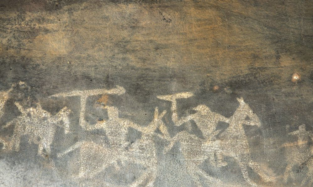 A prehistoric cave painting in Bhimbetka -India , a world heritage site which shows men on their horses going out for hunting.