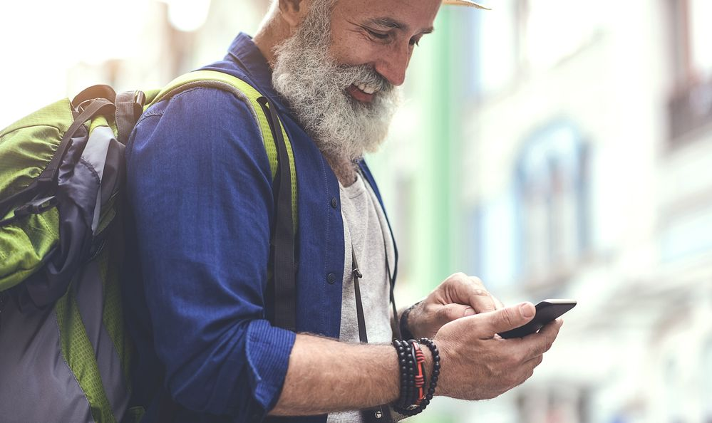 senior male tourist using mobile phone