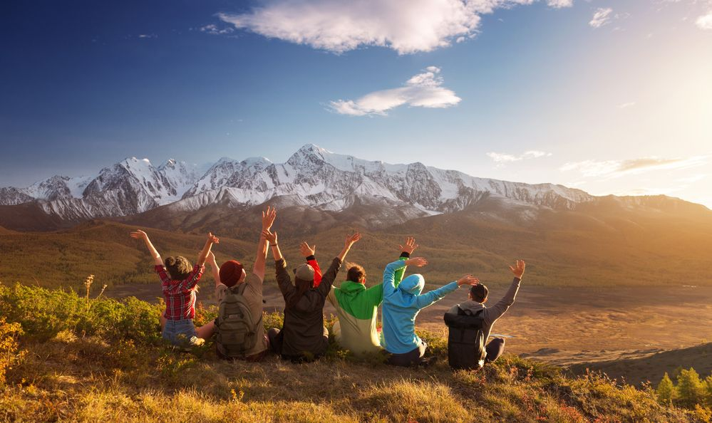 Group of six happy friends is having fun at mountain top
