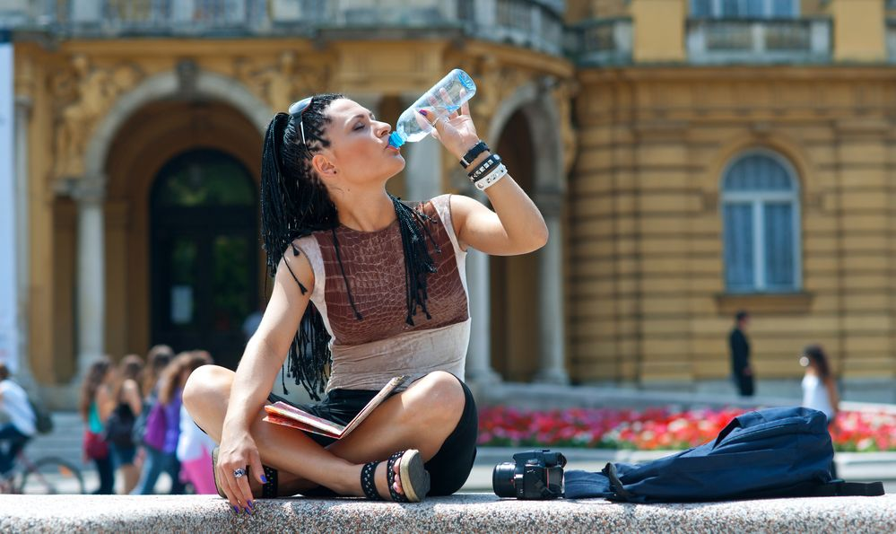 woman tourist drinking from water bottle and relaxing