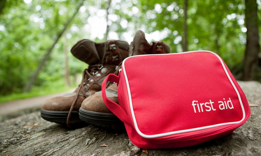 First aid kit and hiking boots in the woods