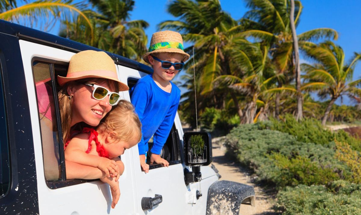 Family driving an off-road car on tropical beach with palms