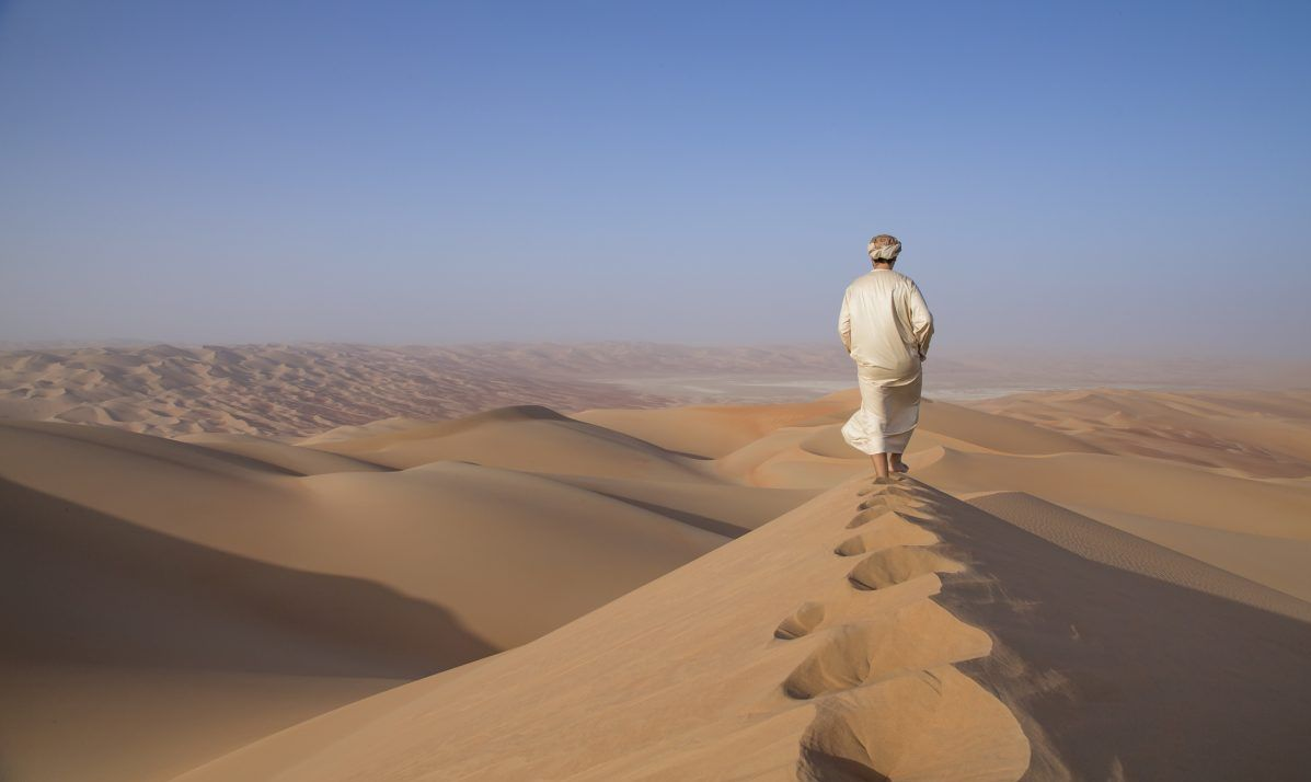 Man in kandura in a desert at sunrise