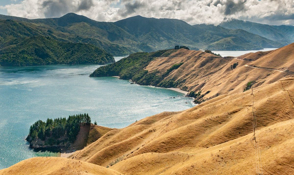 View of the farmland and forested hills leading to French Pass, Marlborough Sounds, at the northern tip of the South Island New Zealand with d'Urville Island beyond the Pass in the distance