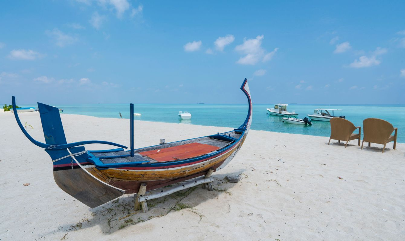 Moldaves traditional boat on white sand beach with turquoise azure water and blue sky with fee clouds and lot of boats in background on small island not far from Maafushi island in Indian Ocean