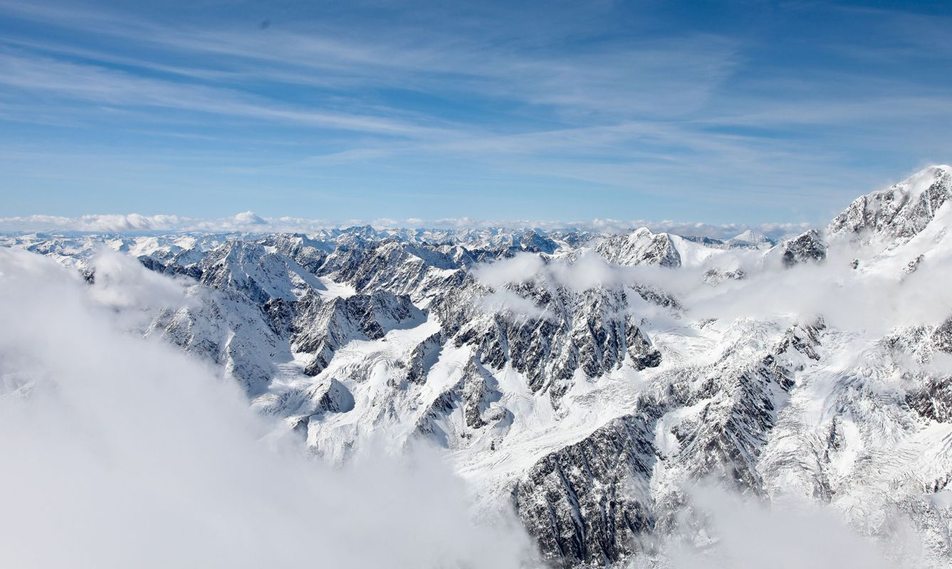 Panoramic view from a high point on the snow-covered mountain range. Mountain Altai.