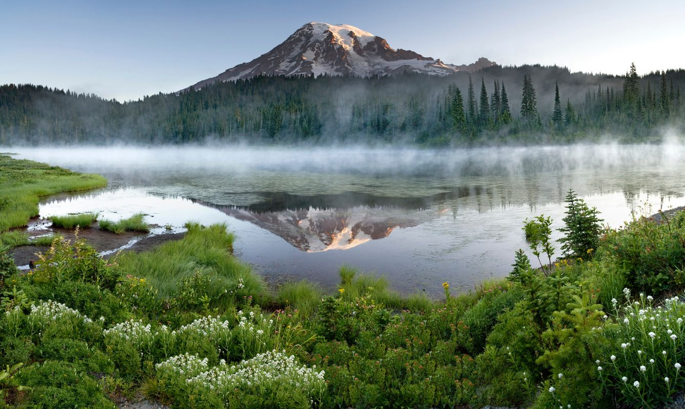 Early morning light illuminates the side of Mount Rainier as mist rises off of Reflection Lake.