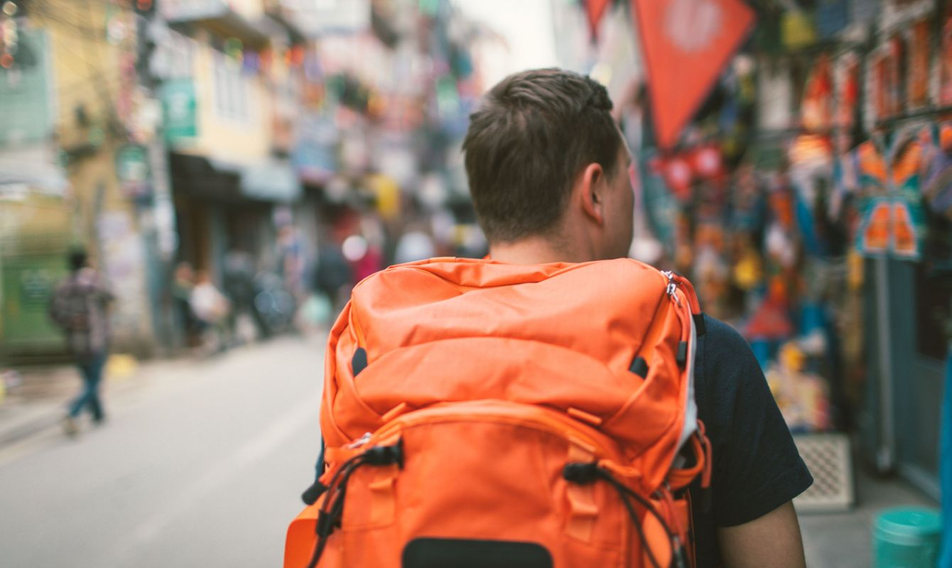 Photo of a tourist, travelling by foot and eager to learn about local lifestyle