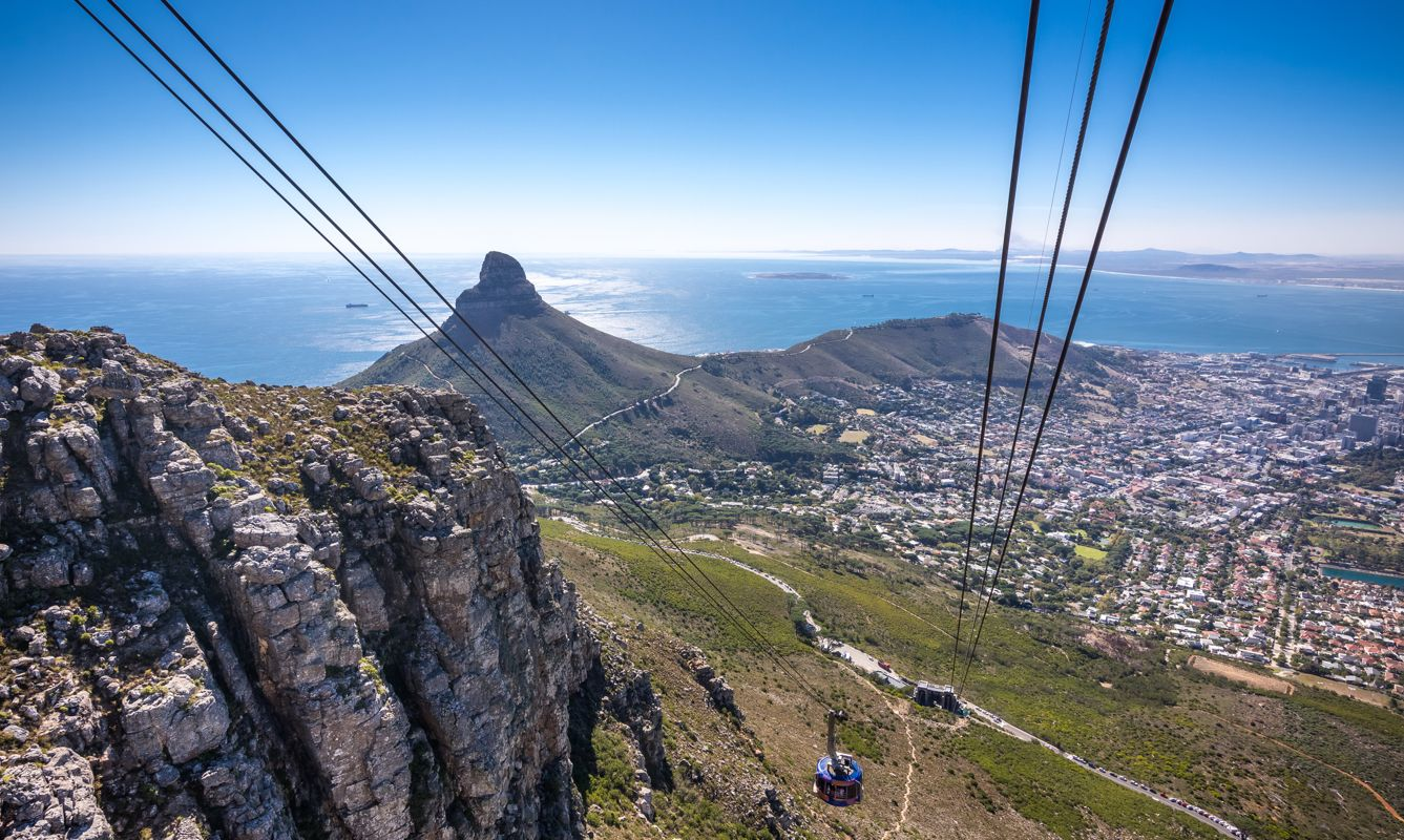 View of the cable car going up Table Mountain with a dramatic landscape of Cape Town.
