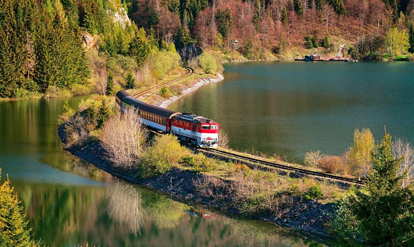 Train passing through lake near Mlynky village in the Slovak Paradise (Slovensky raj) national park, Slovakia.