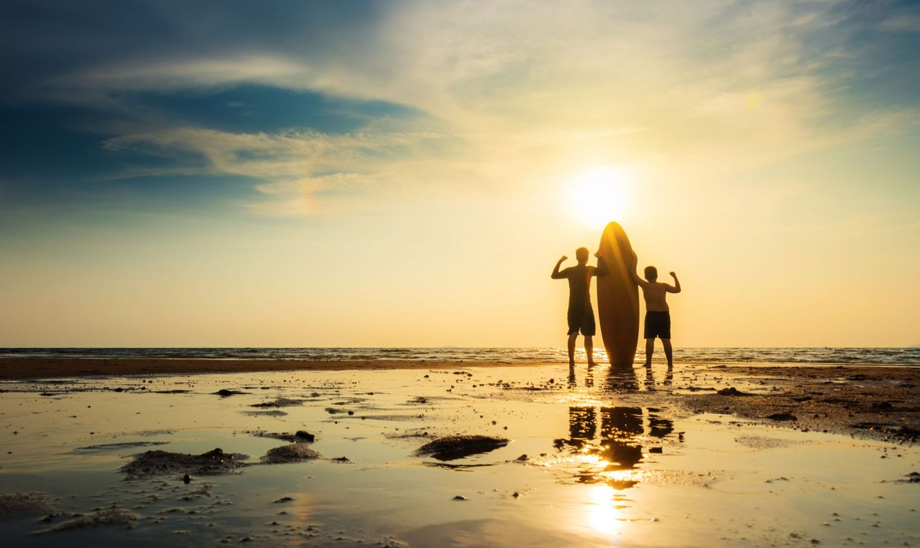 Silhouette of surf man with a boy stand with surfboard, hand up