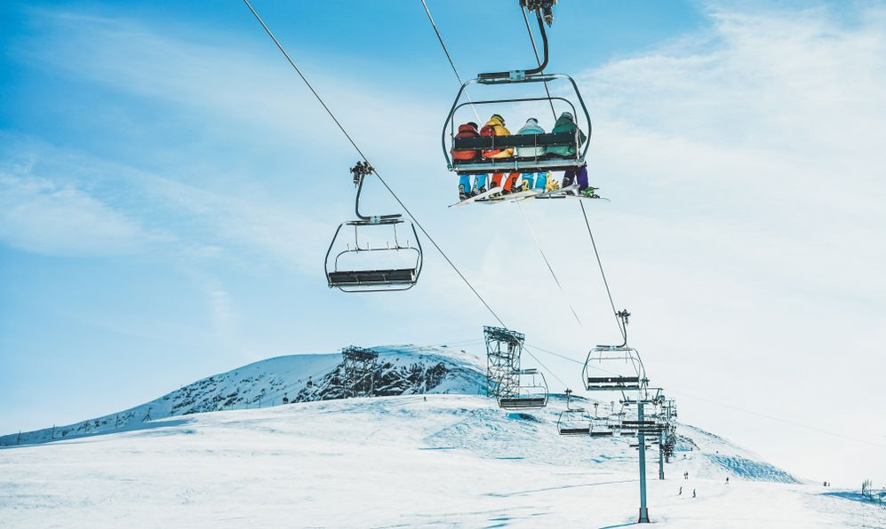 People on ski lift in winter ski resort -