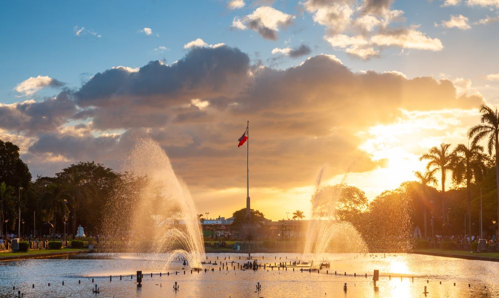 View of a fountain in Rizal Park with a flag of the Philippines under beautiful sunset light, Manila, Philippines.