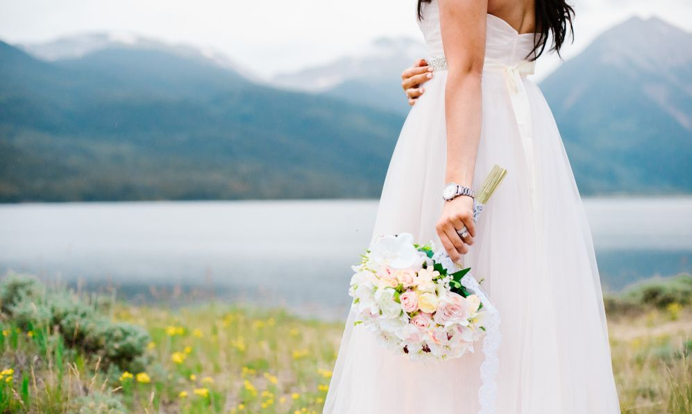 Bride in off white wedding dress holding the bridal bouquet and looking toward the mountains and the lake.