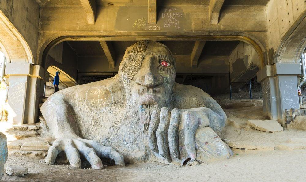 scene of a big sand troll sculpture under the Aurora bridge