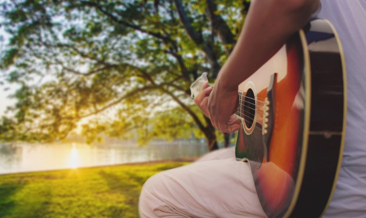 Close up of man hands playing classic guitar in the park at the sunset. warm retro tone , music, lifestyle ane relax concept