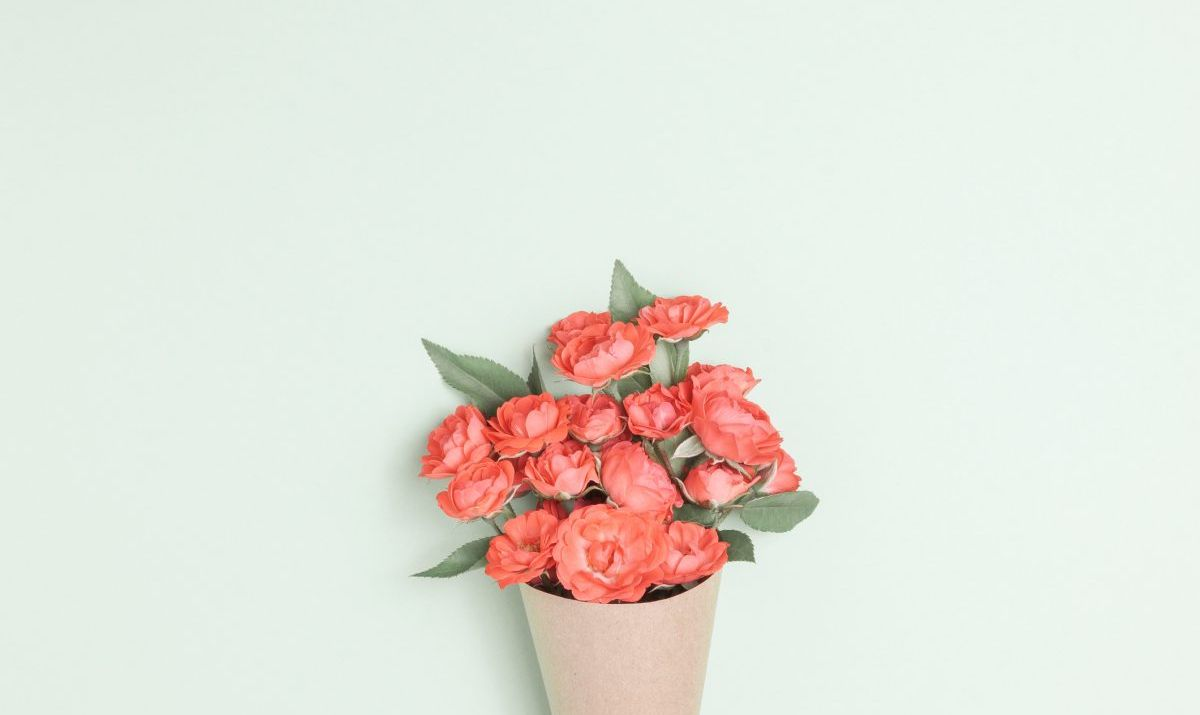 Bouquet of small red roses in vintage paper on the table.