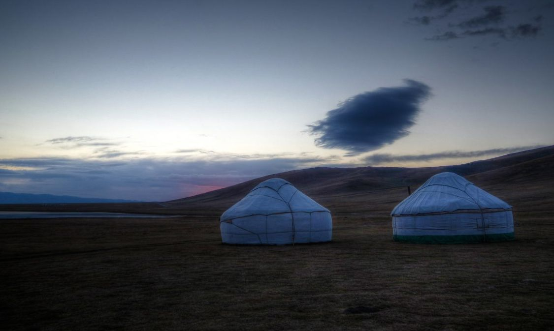 Cloud over the yurts at the shore of Song Kol Lake at the dawn, Kyrgyzstan - stock photo