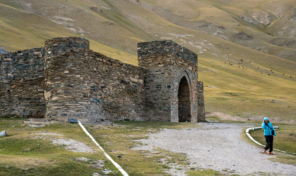 Senior woman walking from Tash Rabat a caravanserai on Silk Road near the border with China, Kyrgyzstan - stock photo
