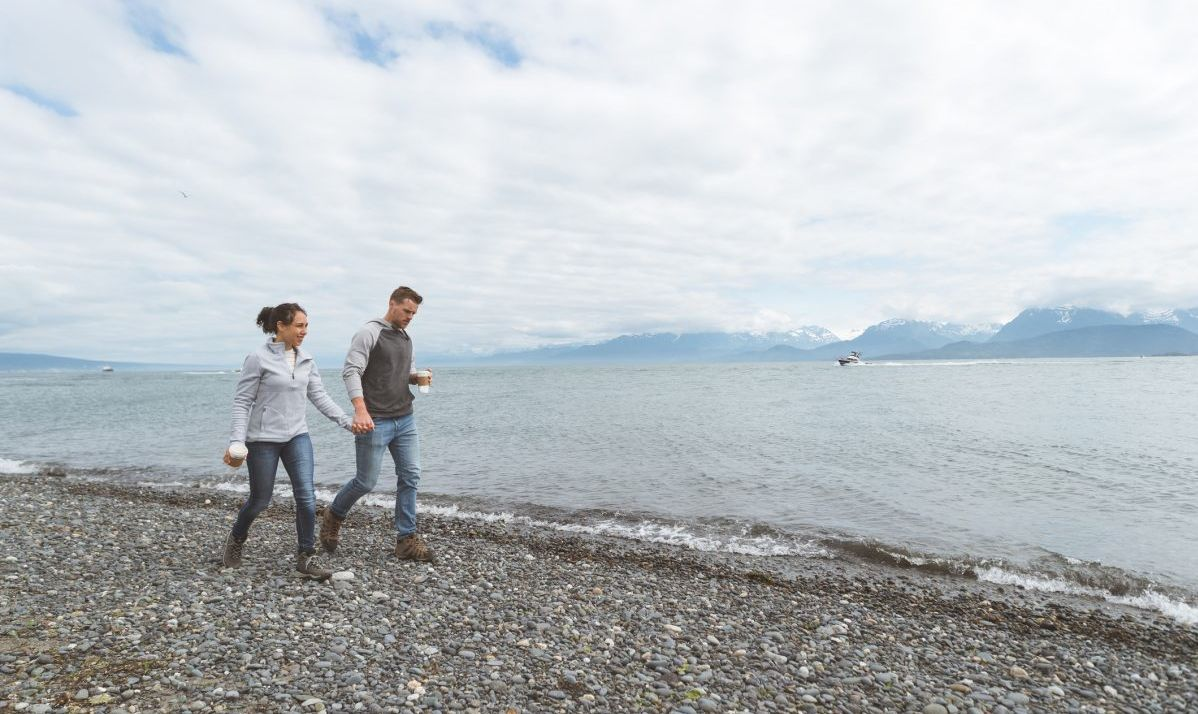 Young couple walking along a rocky ocean bay