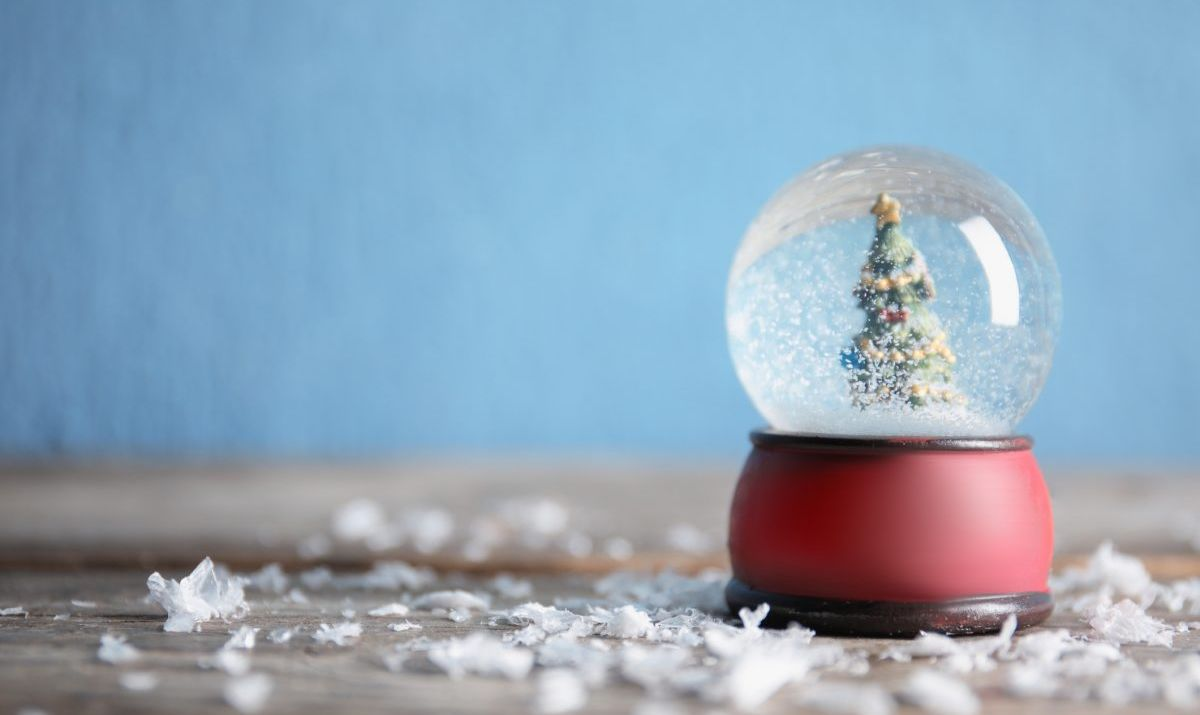 Magical snow globe with Christmas tree on wooden table against color background. Space for text