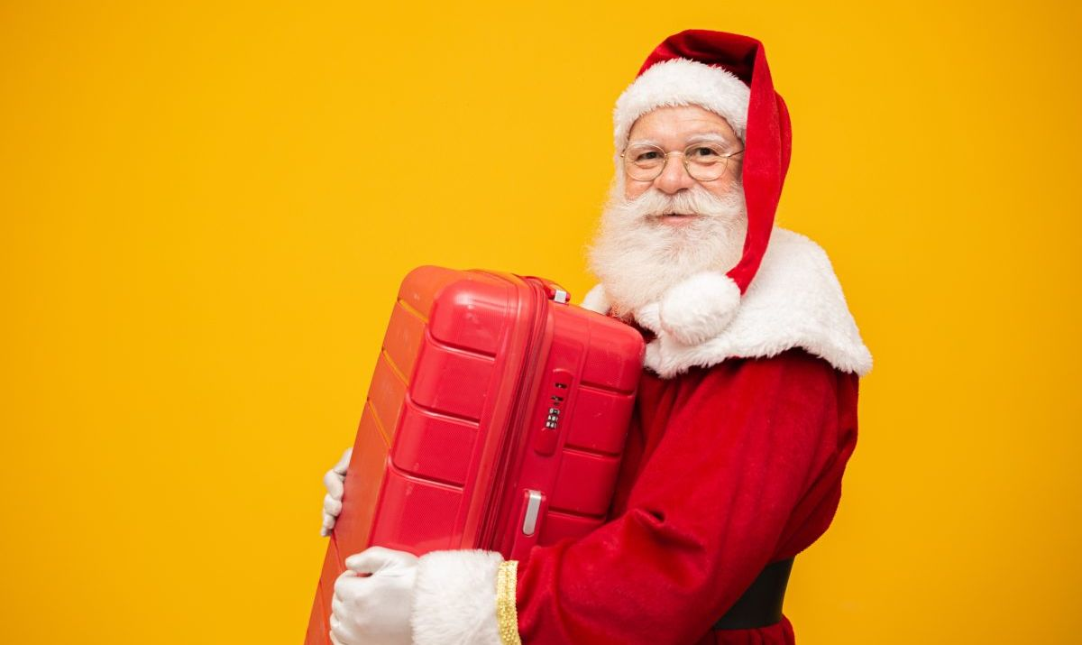 Santa Claus with his suitcase. New Year's travel concept.