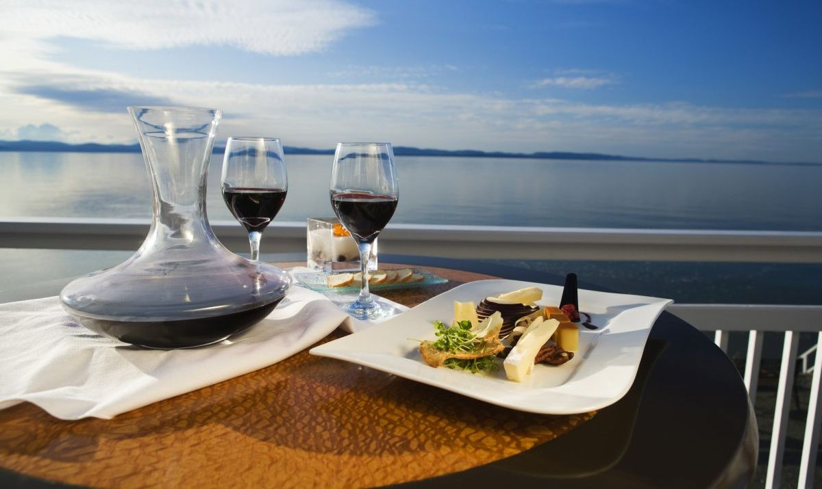 Outdoor dining with wine overlooking the water