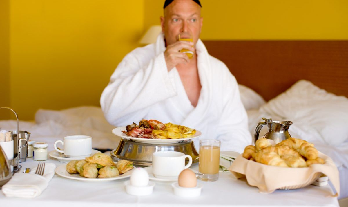 Mature man having breakfast in hotel room